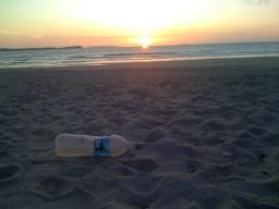Garrafa de plástico na praia ao por do sol