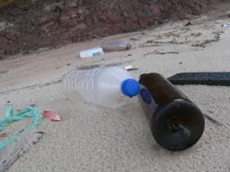 Garrafas de vidro e plástico na praia.